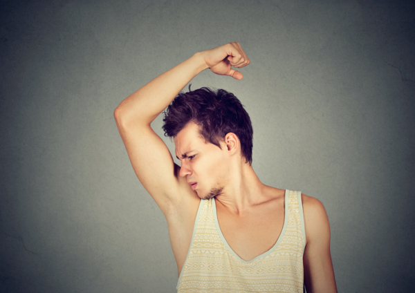 man sniffing his armpit something stinks bad odor