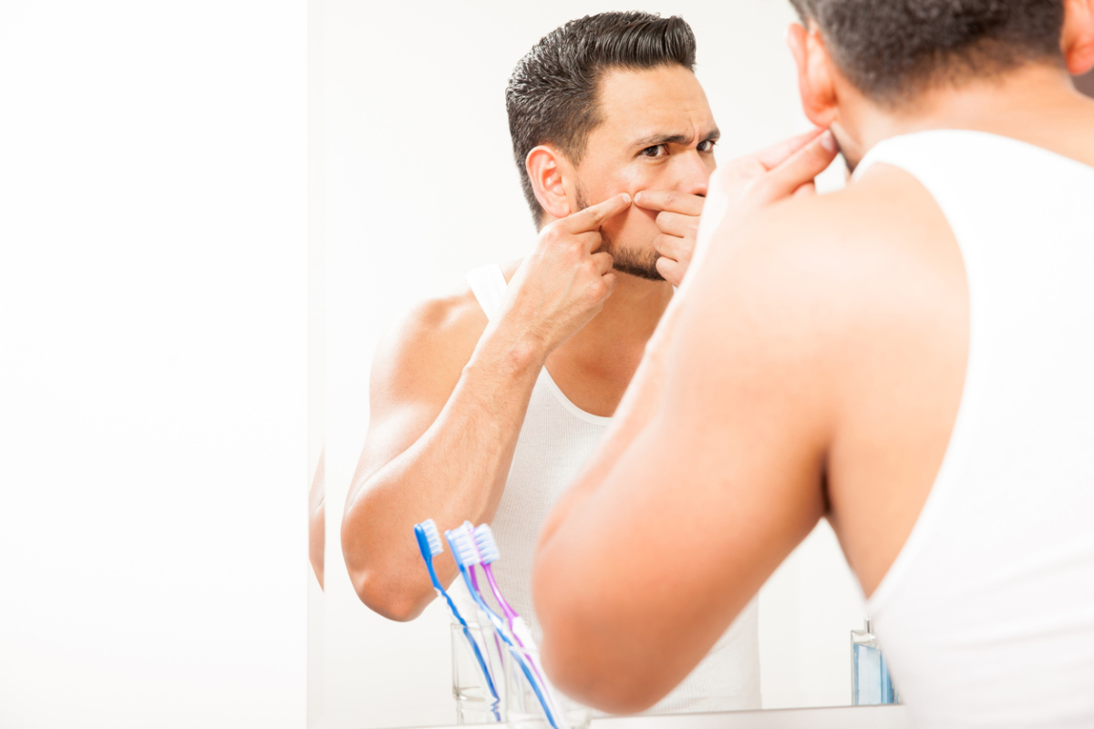 Young man squeezing a pimple