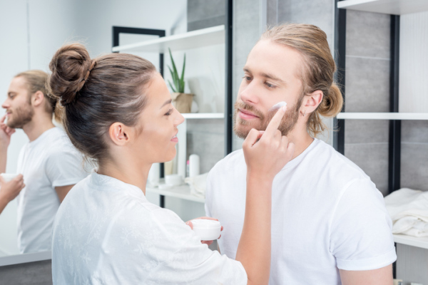 Smiling young woman applying face cream to bearded husband in bathroom